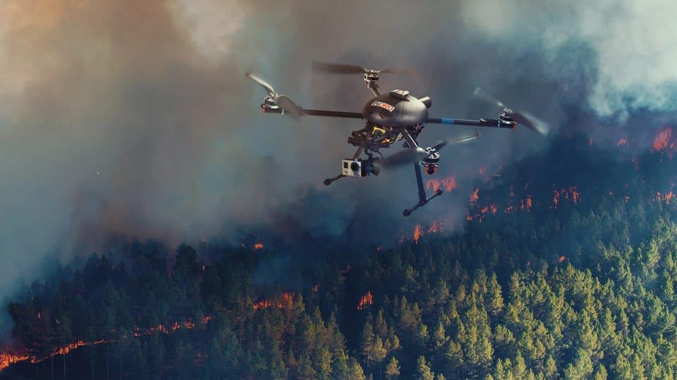 A small UAV is shown surveying the movement of a forest fire. The EOAMS would allow first responders to deploy drones at disaster scenes without endangering other emergency response aircraft or commercial flights. [photo illustration by Kongsberg Geospatial