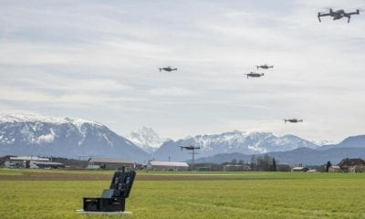 Photogrammetry Swarm in action, with five MP drones in swarm formation hovering above the transport container during a test flight in 2018; a sixth drone is filming the swarm.